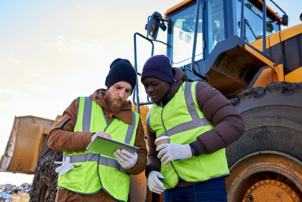 Two men looking at data in mining operation